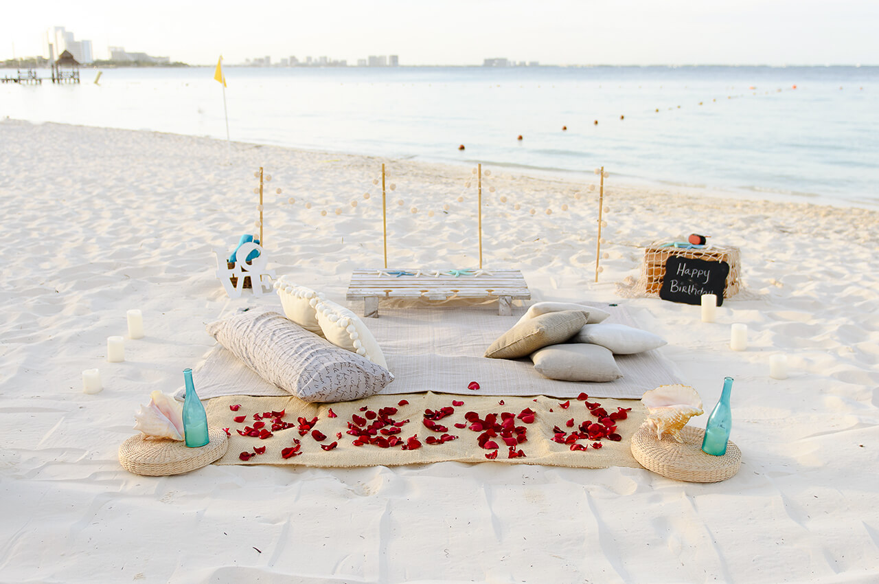 Cancun picnic white boho setup with rose petals